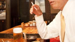 喫煙と飲酒するサラリーマン男性