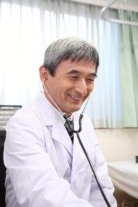 聴診器で診療中のベテラン男性医師
